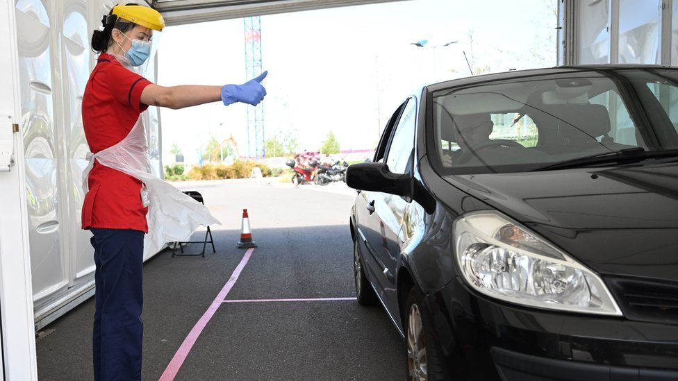 A member of clinical staff wears Personal Protective Equipment (PPE) as she gestures to a key worker at a drive-through test centre for the novel coronavirus at Royal Papworth Hospital in Cambridge on May 5, 2020. - NHS services have come under increased strain with the number of a patients hospitalised and requiring critical care because of the COVID-19 pandemic which has claimed over 30,000 lives in the UK. Mass testing has become a key part of the UK strategy in their battle against the virus.