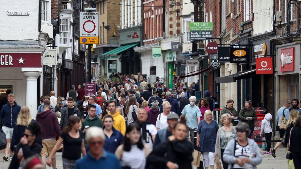 People make their way along the High street in Winchester, Hampshire