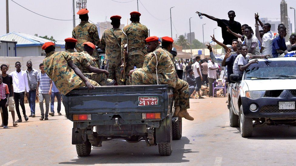 Sudanese demonstrators cheer as they drive towards a military vehicle. Khartoum 11 April 2019