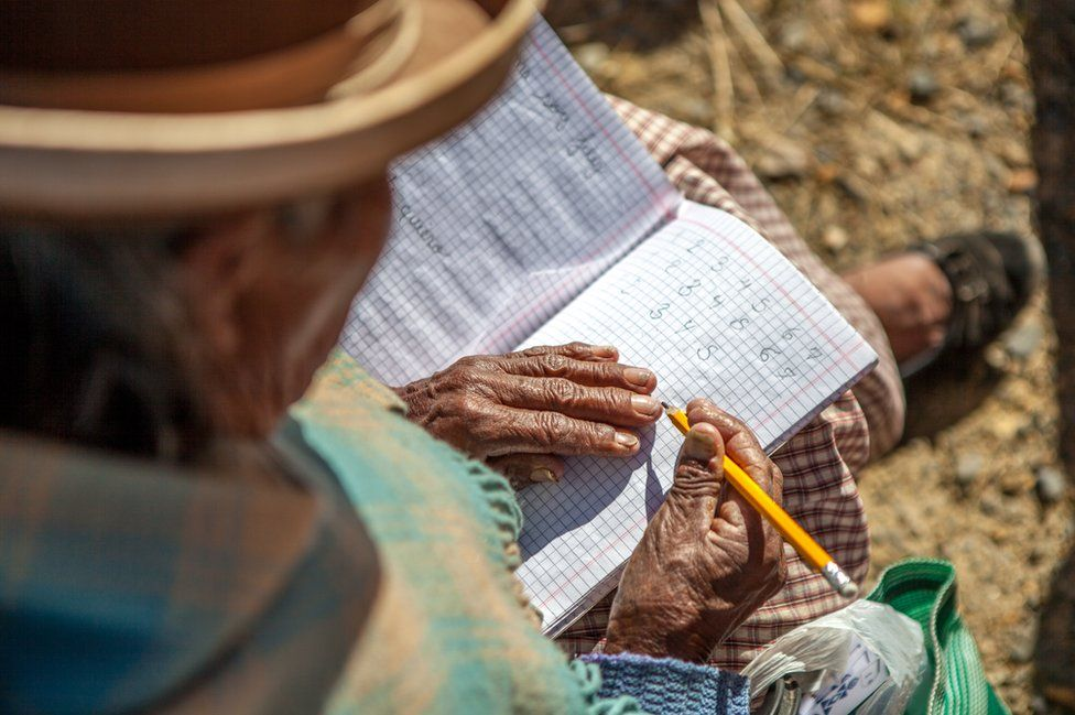 An elderly student writes down numbers from one to seven in a notebook
