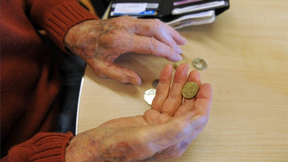 Pensioner's hands holding coins