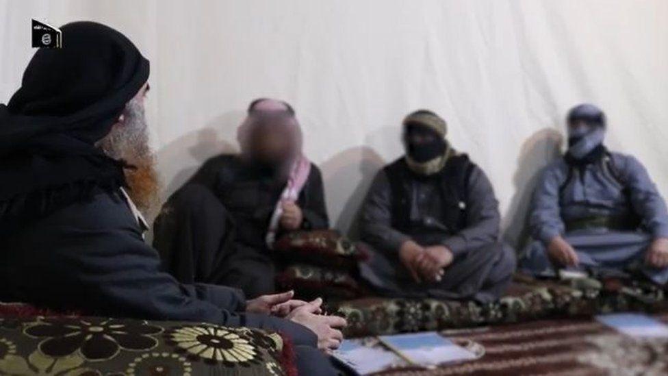 Abu Bakr al-Baghdadi (L) sits with fellow IS members