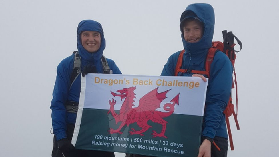 Mike and Matt standing with a flag at the top of Snowdon in the fog