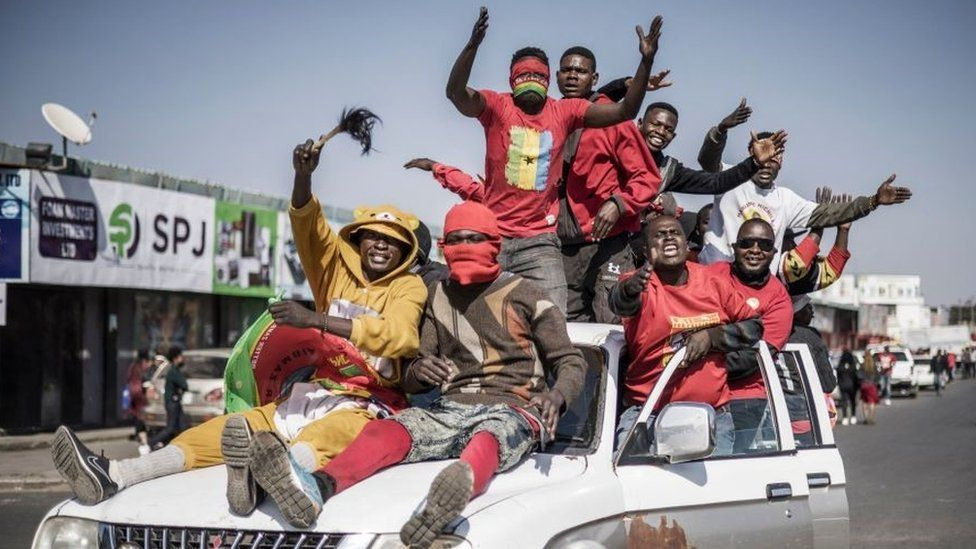 Supporters of Zambian President elect for the opposition party United Party for National Development (UPND) Hakainde Hichilema gestures as they ride on a pick up truck in the streets of Lusaka on August 16, 2021.