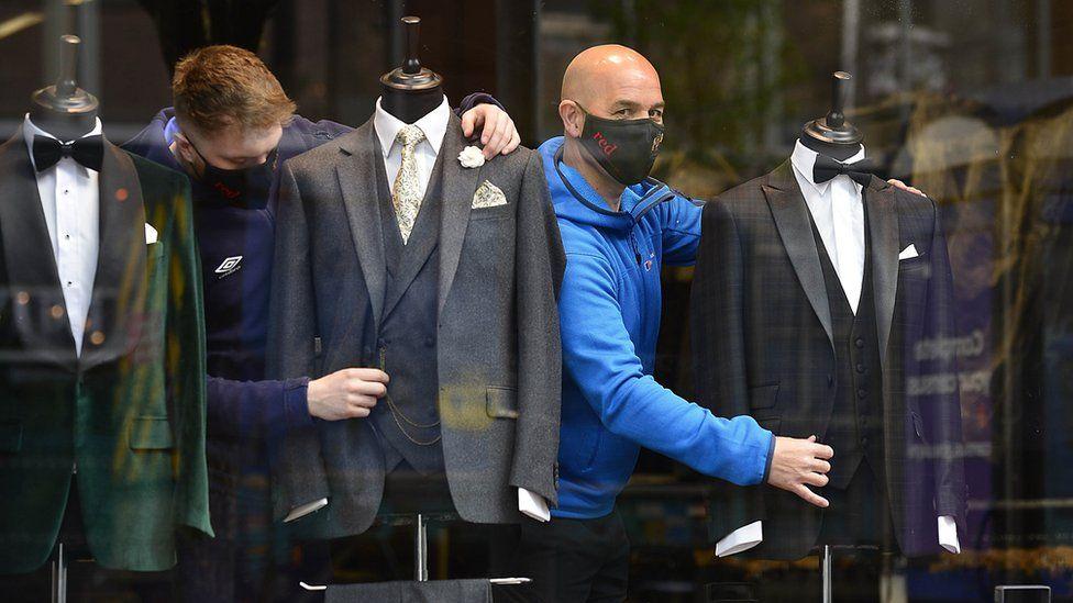 Shop attendants dress mannequins in Belfast suit shop