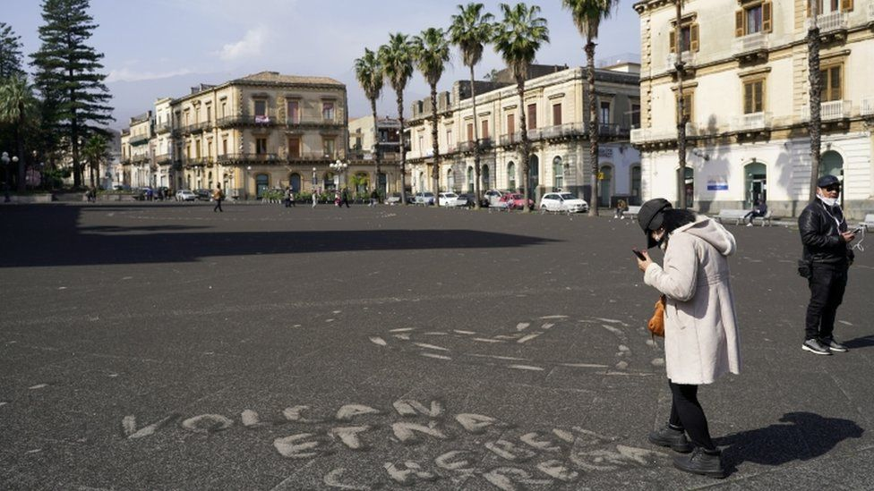 """A person stands next to a sign made with ashes from Mount Etna that reads """"Etna volcano what a nice gift"""" in Giarre, Italy, February 28, 2021"""