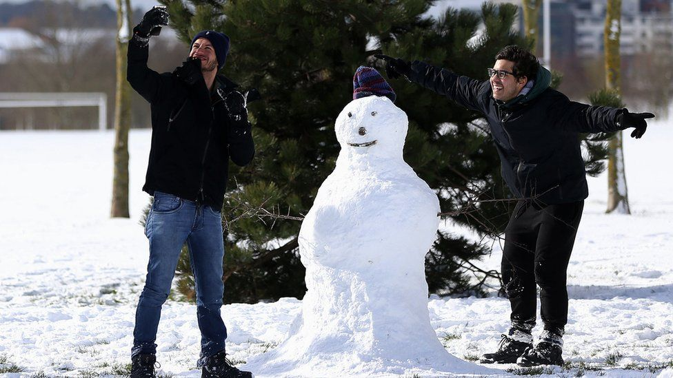 """Weriskles Inacio (left) and Matheus Pires, from Sao Paulo, Brazil, take a selfie with their snowman """"Clayton"""" in Tolka Valley park, Dublin, as they enjoy their first time ever seeing snow."""