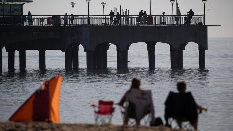 People fish off Boscombe Pier in Dorset