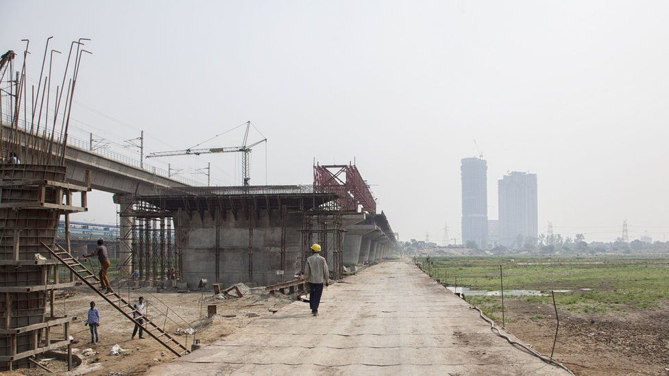 An Indian worker walks on a temporary bridge at a construction site along the Yamuna River in New Delhi on May 28, 2018