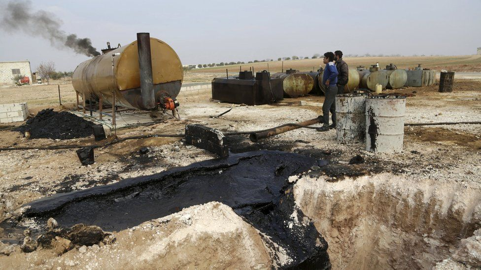 Men work at a makeshift oil refinery site in Marchmarin town, southern countryside of Idlib, Syria December 16, 2015.