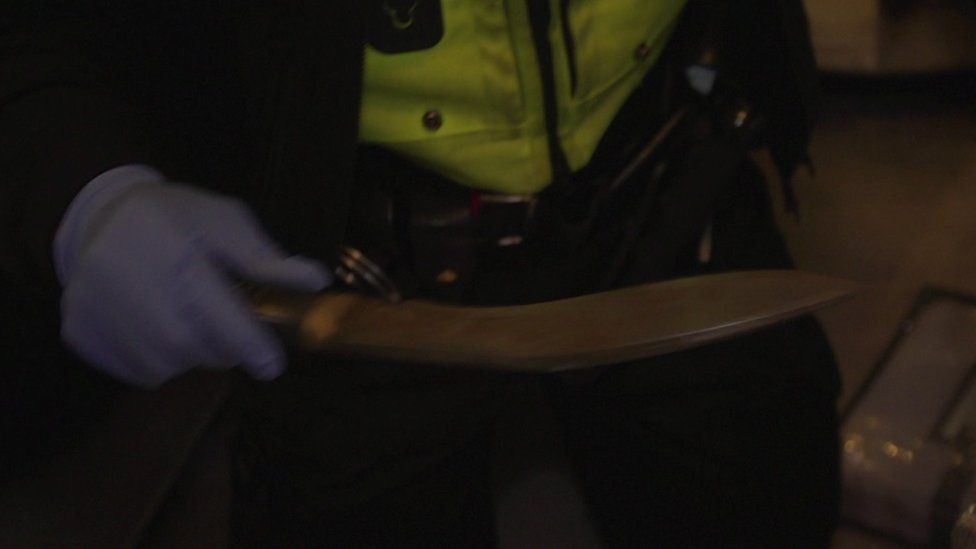 Police officer holding knife