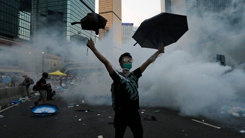 A protester raises umbrellas as tear gas is fired by riot police to disperse protesters outside the government headquarters in Hong Kong (28 September 2014)