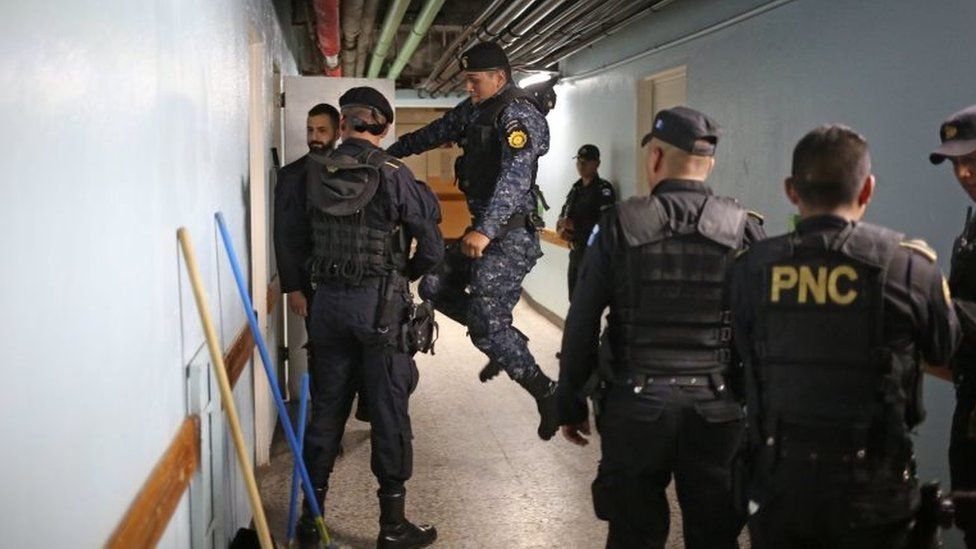 Police kick down a door inside Roosevelt Hospital searching for gunmen after an armed attack in Guatemala City, Guatemala, 16 August 2017.