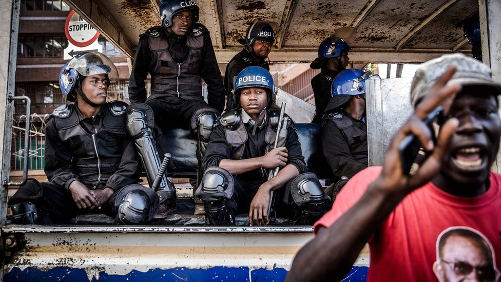 Zimbabwean anti riot police officers observe a supporter of the opposition party Movement for Democratic Change (MDC) who is taking part in a protest against alleged widespread fraud by the election authority and ruling party, after the announcement of the election's results, outside the Zimbabwe Electoral Commission (ZEC) headquarters in Harare, 1 August 2018