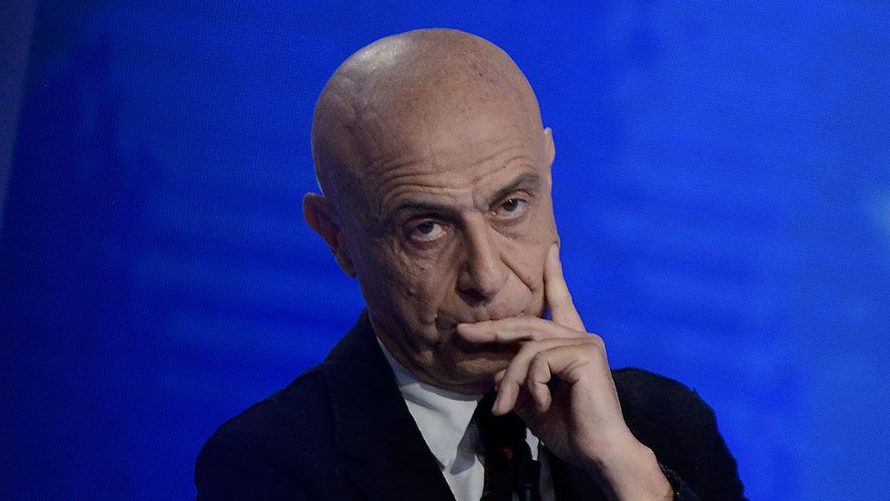 Marco Minniti is pictured against a bright blue background, one hand against his face in a pensive pose