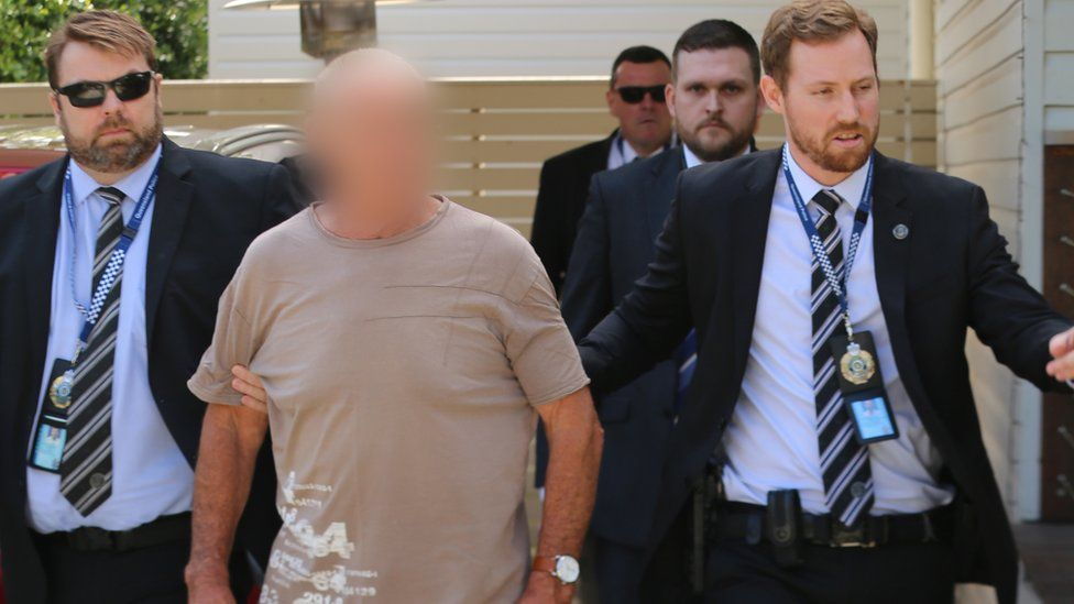 New South Wales police arresting Chris Dawson, who's face is blurred out