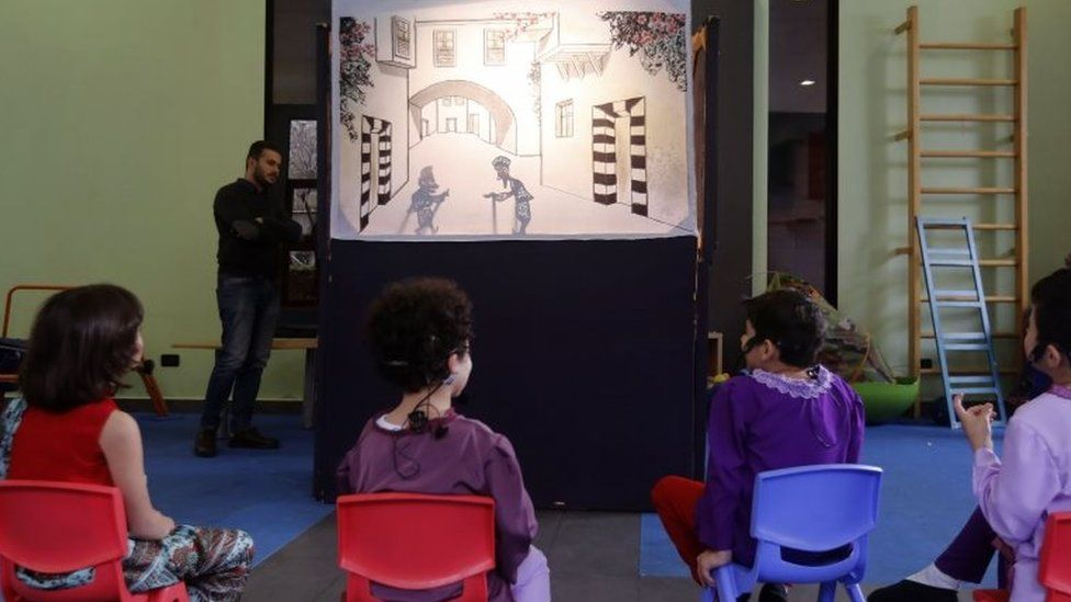 Syrian children watch a performance by the country's last shadow puppeteer Shadi al-Hallaq in Damascus on 3 December 2018.