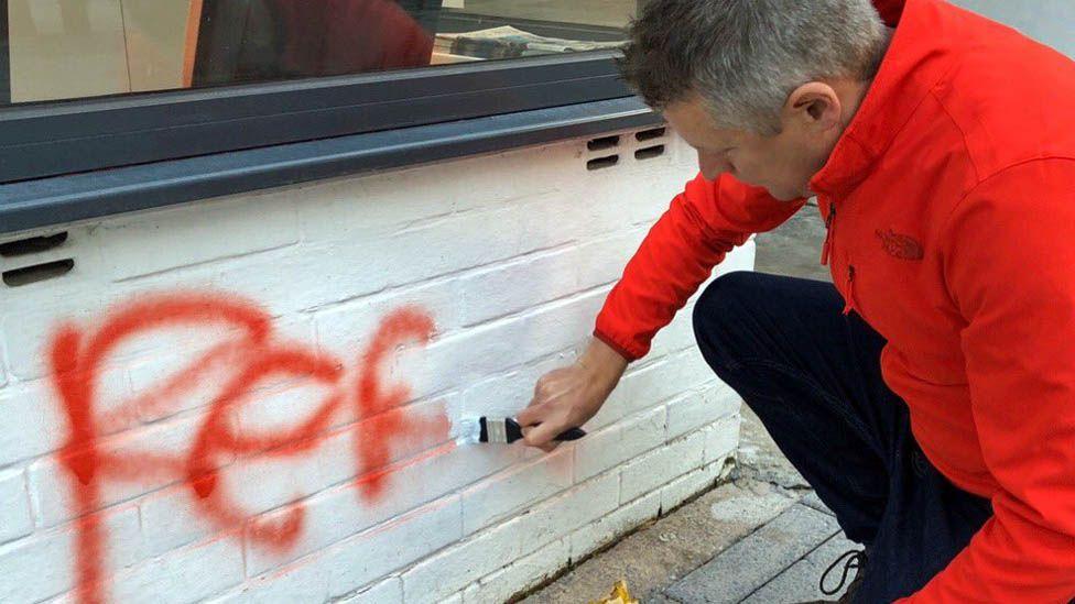 Luke Pollard painting over graffiti outside his office
