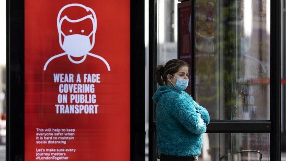 Woman at bus stop wearing a face mask
