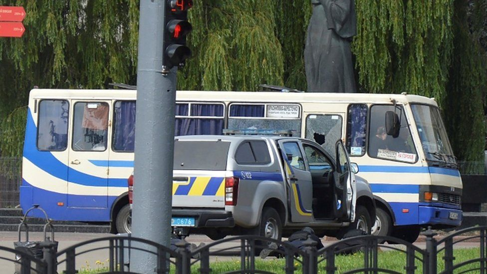 Ukrainian law enforcement officers lie on the ground behind a car near a passenger bus, which was seized by an unidentified person in the city of Lutsk, Ukraine July 21, 2020