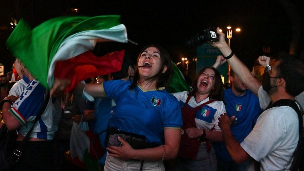 Supporters of the Italian national football team celebrate after Italy beat England 3-2 on penalty shootout to win the the UEFA EURO 2020 final football match, at the Fori Imperiali fanzone, in Rome