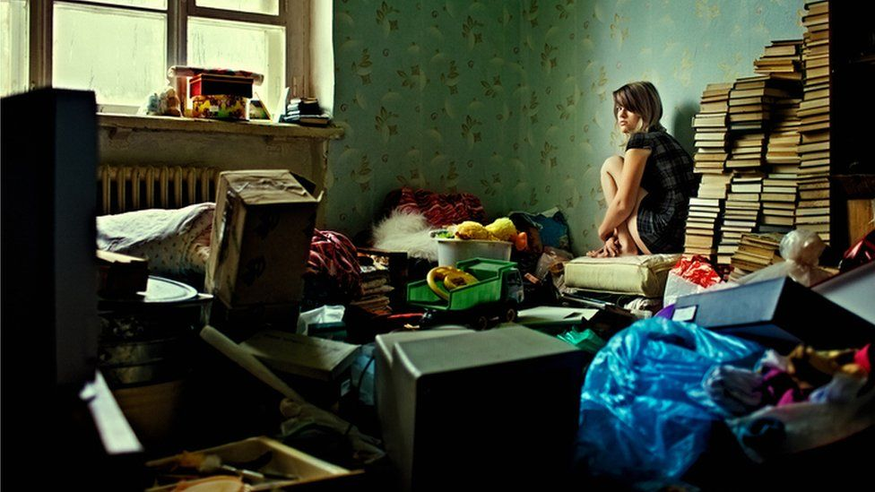 Girl in cluttered room