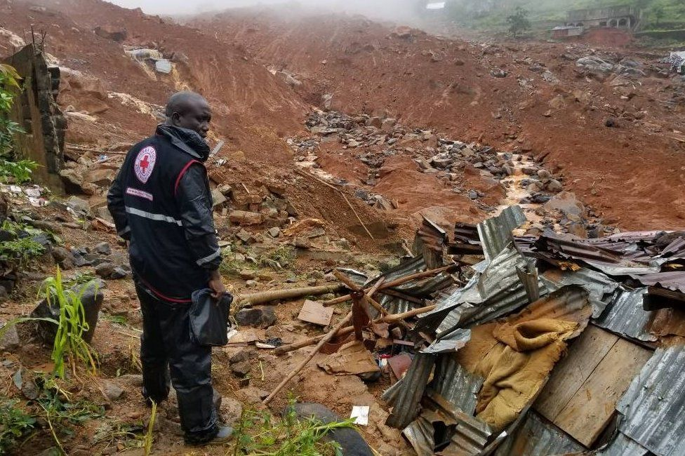 A Red Cross worker looks out across the wreckage of the mudslide