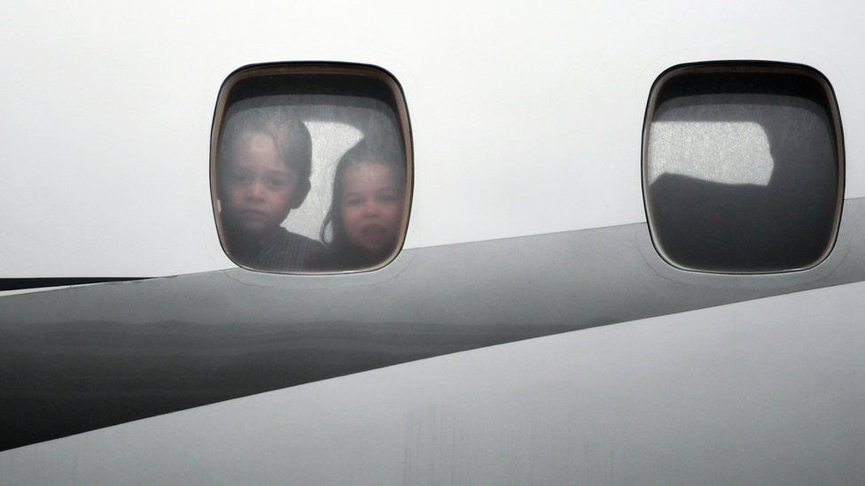 Charlotte and George look out of the window of the plane before disembarking