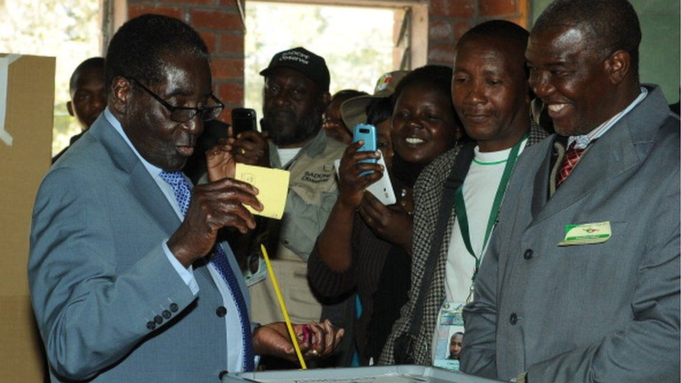 Zimbabwe President Robert Mugabe (L) casts his vote at a polling booth in a school in Harare on July 31, 2013.