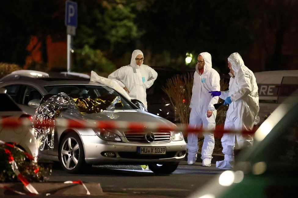 Forensic experts examine a damaged car after a shooting in Hanau near Frankfurt, Germany, 20 February 2020.