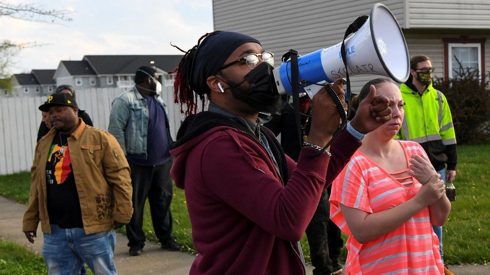 Crowds react as investigators work at the scene where Ma'Khia Bryant was fatally shot by a police officer in Columbus, Ohio, 20 April 2021