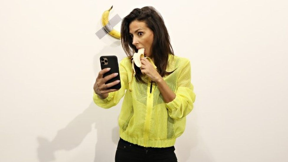 Woman eating banana takes selfie with a banana taped to a wall that sold for $120,000