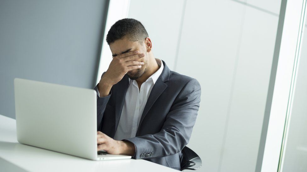 Businessman looking frustrated while using a laptop
