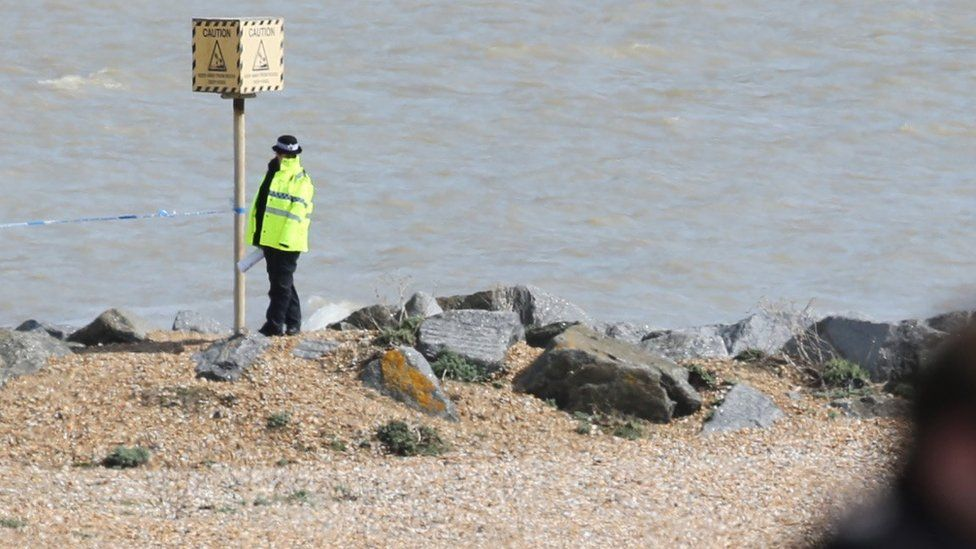 A lone police officer stands on the beach at St Leonard's