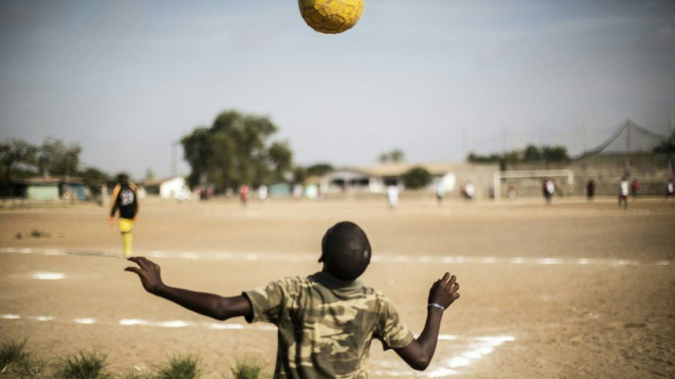 A Liberian boy plays with a ball as international Liberian football star, George Weah plays a match on a dusty pitch at the Alpha Old Timers Sports Association in Paynesville in Monrovia on April 30, 2016