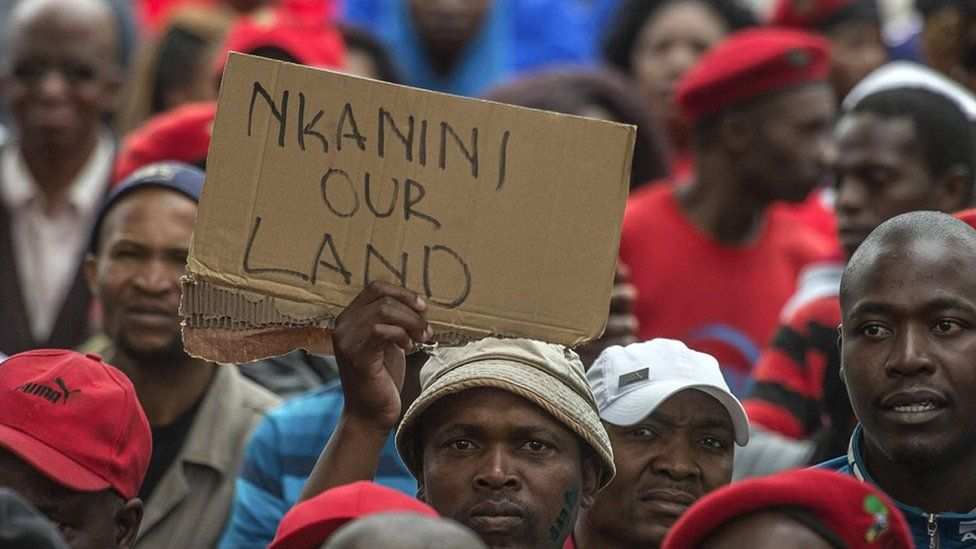 """South African opposition protest in 2016 with someone holding up a sign reading """"Nkanini our land""""."""