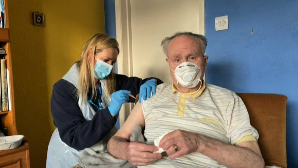 A housebound gentleman receives a vaccine jab in his front room