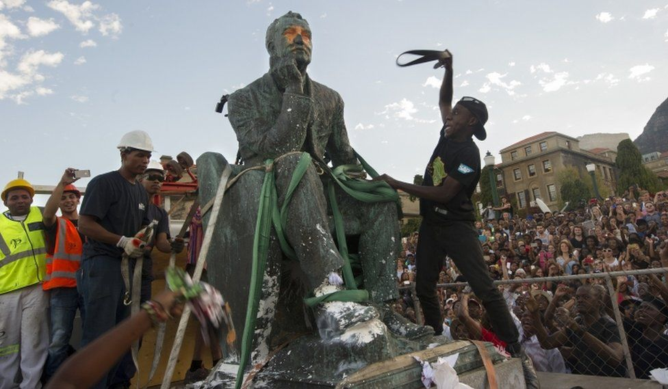 Students attack the defaced statue of British mining magnate and politician, Cecil John Rhodes, as it is removed by a crane from its position at the University of Cape Town on April 9, 2015, in Cape Town.