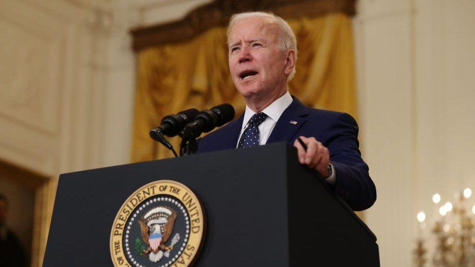 Joe Biden speaking at a presidential podium.