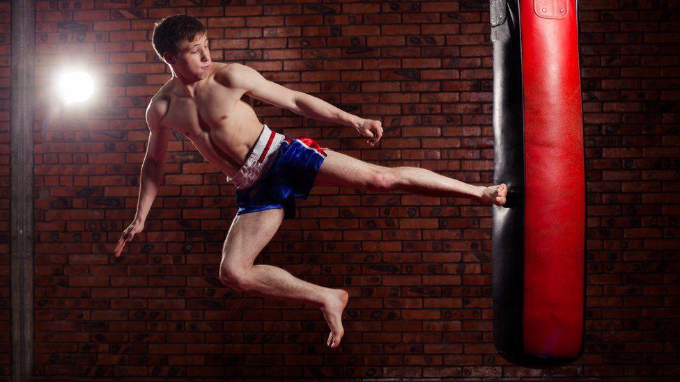 Man in shorts kicking a punchbag