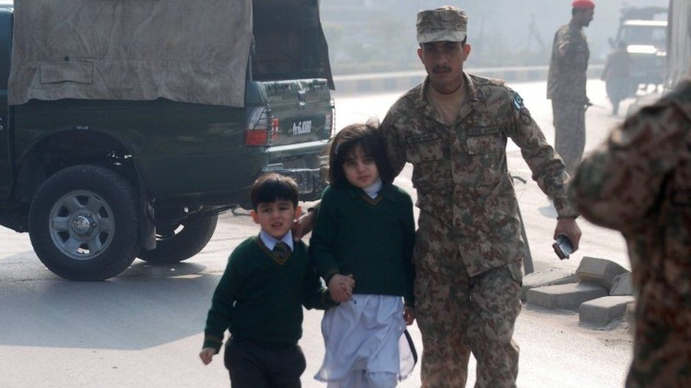 A Pakistani soldier escorts schoolchildren from the Army Public School when it was attacked by Taliban gunmen in Peshawar (16 December 2014)