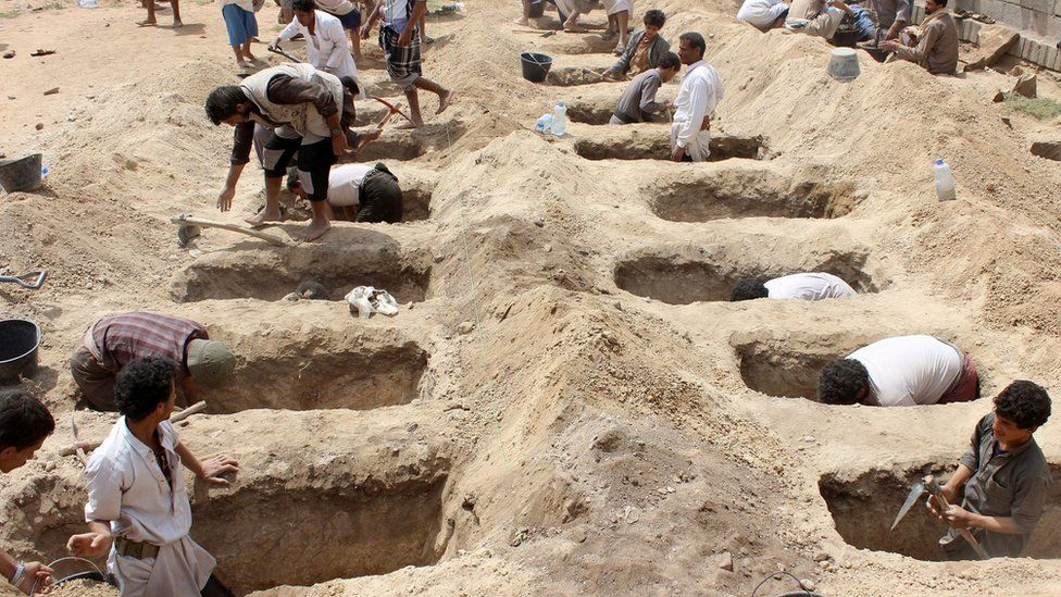 Yemenis dig graves for children in the wake of an air strike on a bus in Saada province