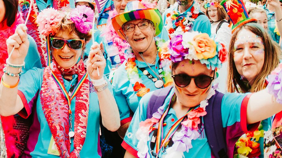 People wearing rainbow hats and flower garlands at Pride In Hull event