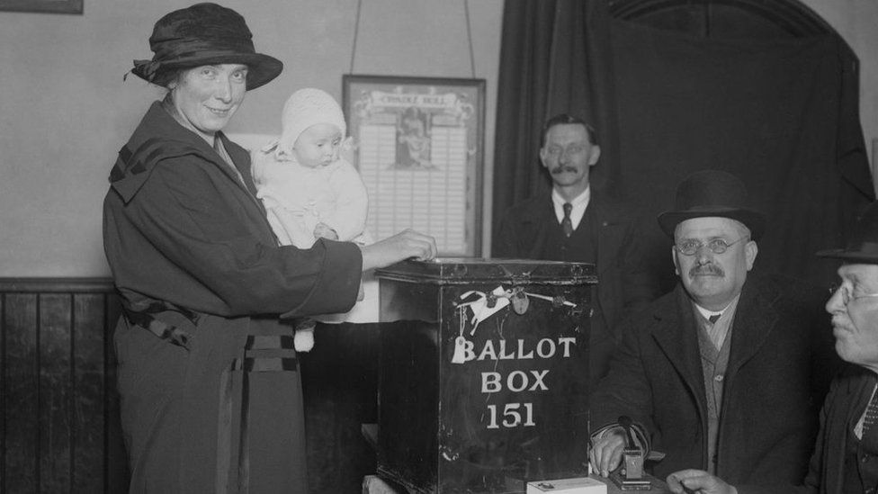 A mother casts her vote in the 1923 election