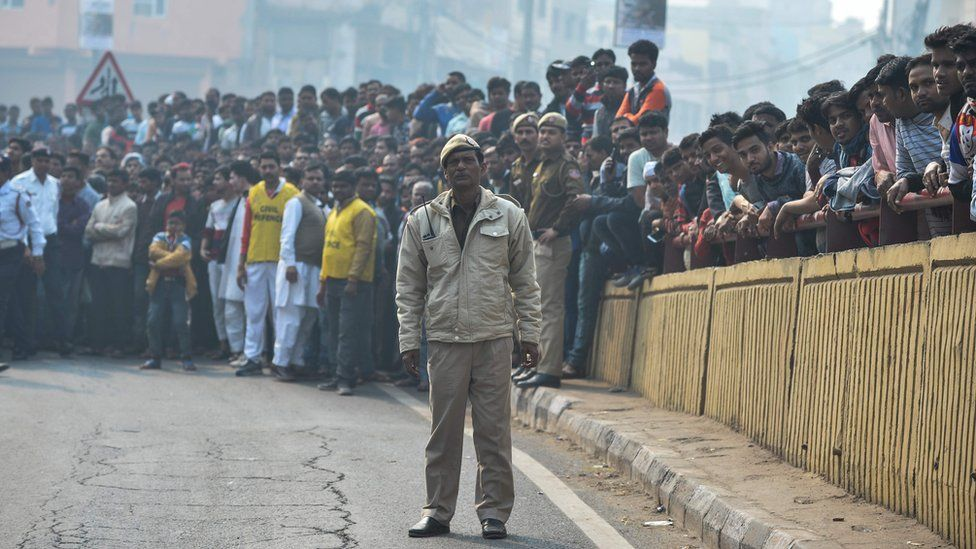 A policeman and onlookers gather near a factory fire in Delhi
