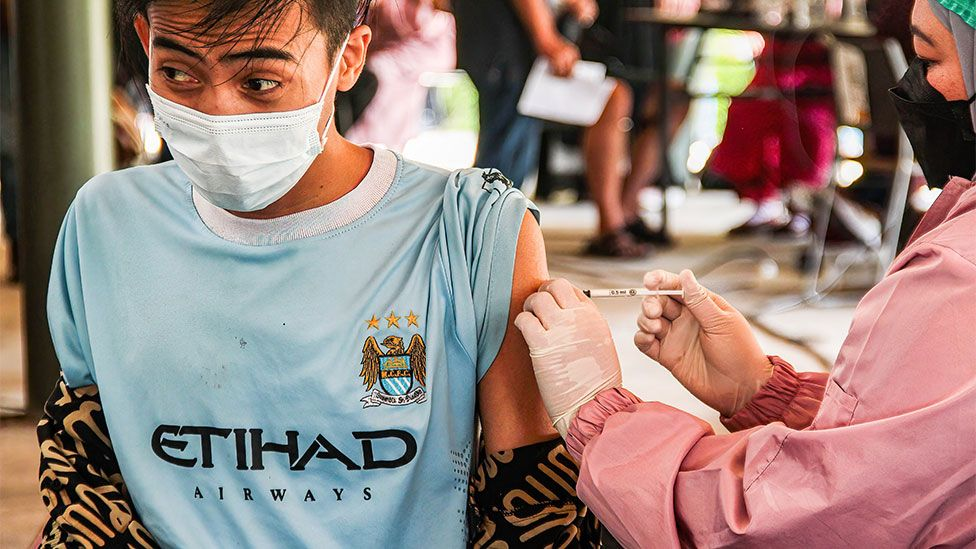 A man gets vaccinated in Indonesia