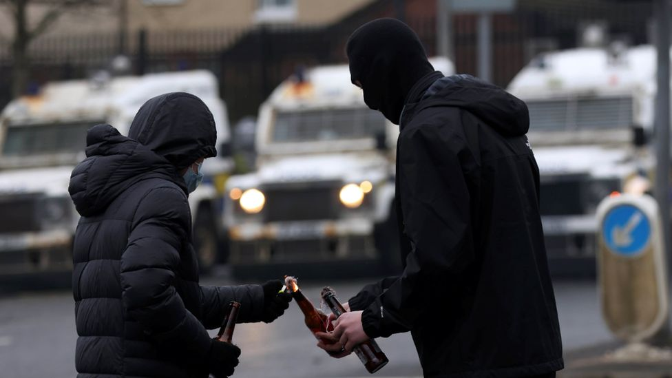 Two young men with their faces covered standing in the foreground, with a row of police Land Rovers in the middle distance. One of them is lighting a petrol bomb which the other one is holding in his hand