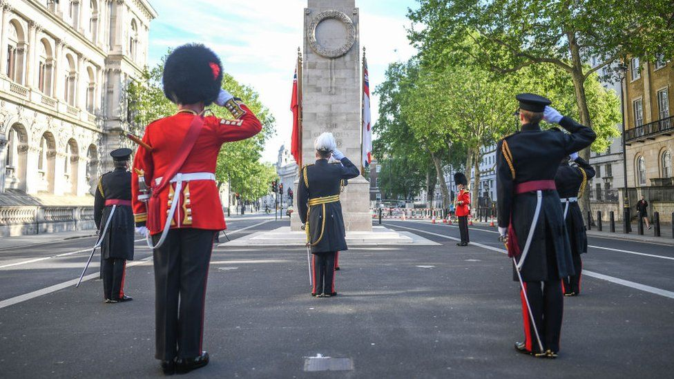 Members of the armed forces are seen saluting during a service at the Cenotaph on Whitehall