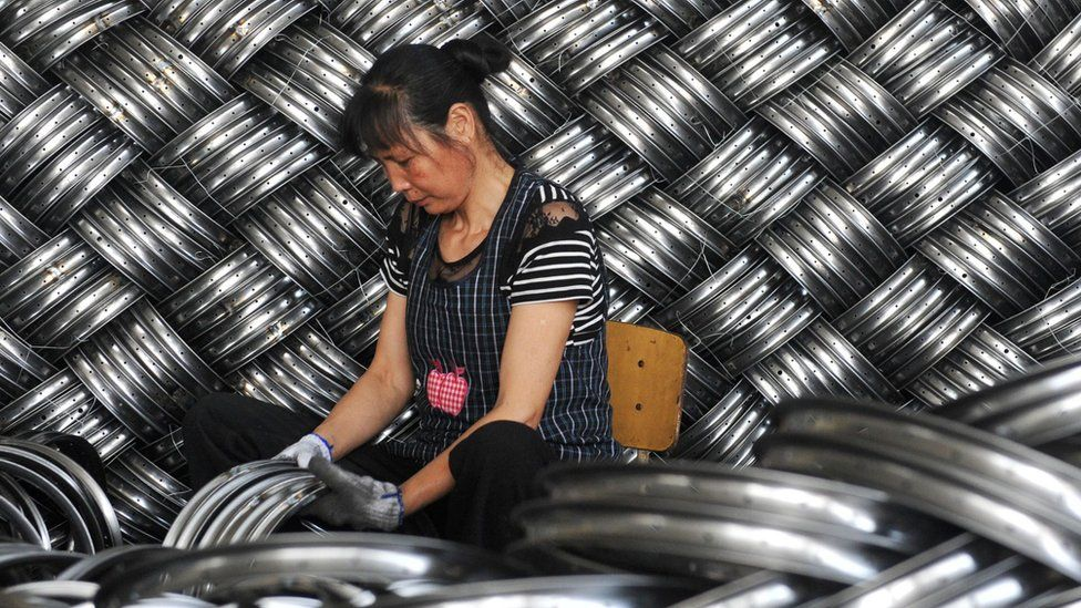 A woman works in a steel hub factory in China