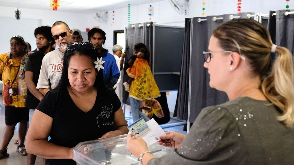 A woman casts her vote at a polling station in the referendum on independence on the French South Pacific territory of New Caledonia in Nouméa on 4 October 2020